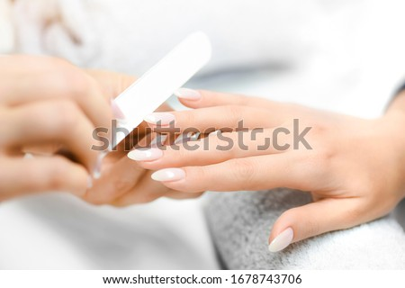 Nails manicure detail with file or brush item. Woman beautiful nail care process. #1678743706