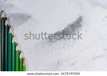 Green pencils on a white stone table #1678749304
