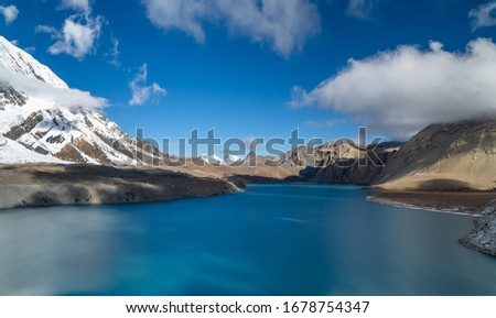 Blue Lake surrounded by mountains and clouds #1678754347