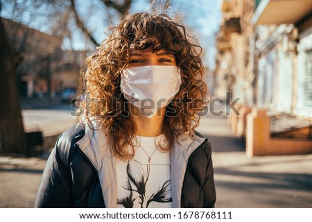 Happy young woman wearing facial mask for virus protection standing outdoors on sunny spring day. #1678768111