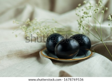 black eggs on a plate with a gold border on a gray linen background. horizontal photo