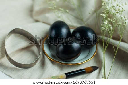 black eggs on a plate with a gold border and a brush on a gray linen background. horizontal photo