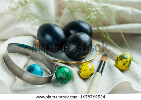 black eggs on a plate with a gold border and next to it multicolored quail eggs on a gray linen background. horizontal photo