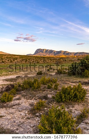 North face of the Pic Saint-Loup, illuminated by the setting sun, in a quasi-desert landscape