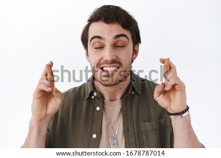 Close-up portrait of hopeful handsome guy wishing all best, close hands and imaging dream come true, positive attitude concept, cross fingers good luck, pleading birthday present, white background