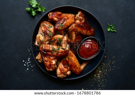 Grilled spicy chicken wings with ketchup on a black plate on a dark slate, stone or concrete background. Top view with copy space. Royalty-Free Stock Photo #1678801786