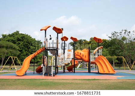 The outdoor playground in the daytime has a backdrop of green trees and blue skies. Royalty-Free Stock Photo #1678811731