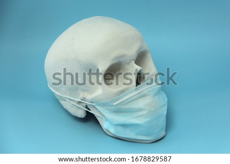 White human skull made of gypsum with a medical mask on a blue background. The concept of a pandemic, medicine and coronovirus. #1678829587