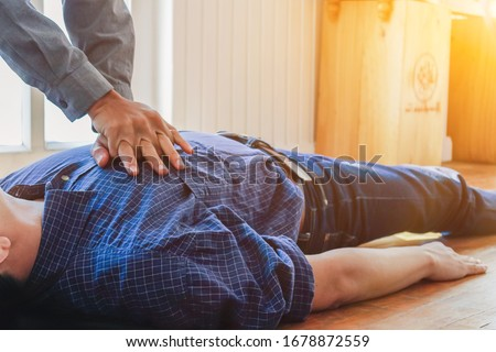 The young man is helping his unconscious friend and stop breathing on the floor with CPR, as he had previously trained to rescue the unconscious and stopped breathing. concept of saving lives with CPR #1678872559