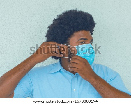 A man in a blue shirt putting on a medical mask to avoid contagion #1678880194