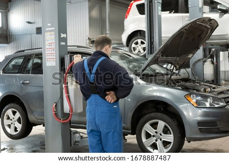 Male mechanic in special uniform. Automobile on mechanical lift in garage. Car service center and professional worker in repairing concept #1678887487