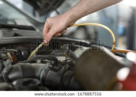 Close up hand of a man in repair shop draining Brake fluid through pipe tank of car for changing fluid. Maintenance concept Royalty-Free Stock Photo #1678887556