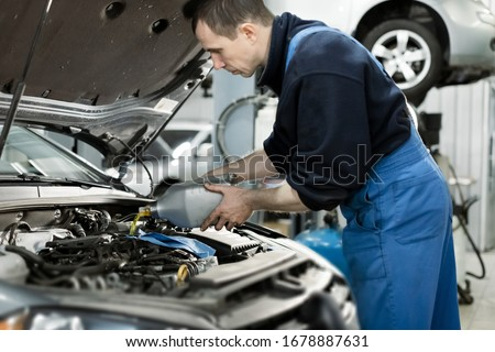 Hand mechanic in repairing car,Change the Oil.Car maintenance, concept. Middle shoot #1678887631