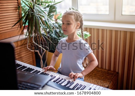 Pretty young musician playing classic digital piano at home during online class at home, social distance during quarantine, self-isolation, online education concept #1678904800