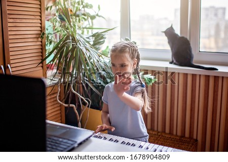 Pretty young musician playing classic digital piano at home during online class at home, social distance during quarantine, self-isolation, online education concept #1678904809