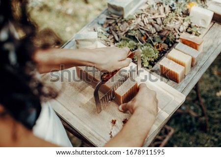 Woman is making handmade natural soaps on an old wooden table Royalty-Free Stock Photo #1678911595
