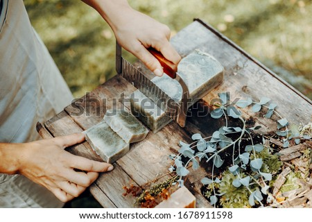 Woman is making handmade natural soaps on an old wooden table Royalty-Free Stock Photo #1678911598
