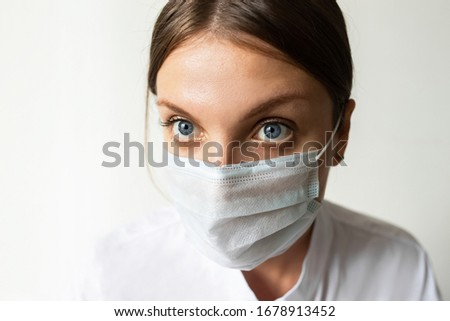 Close up of a female nurse putting on a mask to protect from airborne respiratory diseases such as the flu, coronavirus, ebola, TB, etc copyspace #1678913452