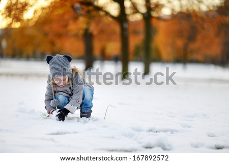 Little girl having fun on winter day in a city