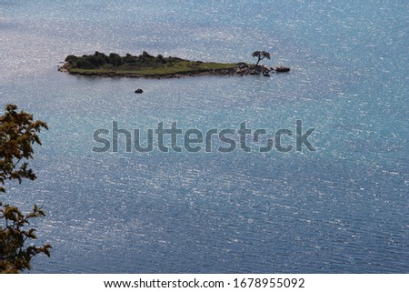 aegean sea some cove with small island has just one tree open water with turquoise and blue  color with same pic
