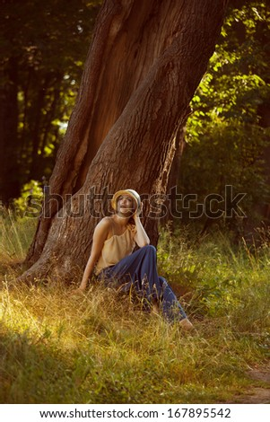 Romantic young woman sitting under a big tree #167895542