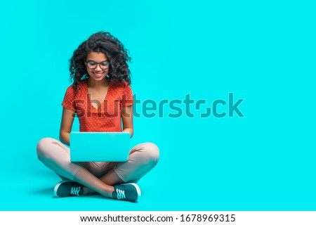 Beautiful young smiling woman in casual outfit and trendy eyeglasses sitting isolated on bright colored blue background and working on her laptop. Full length horizontal studio shot. Copy space.