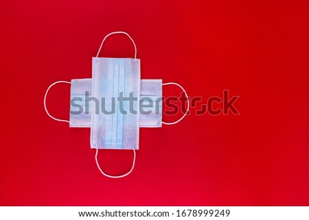 Medical masks in the form of a medical cross on a red background. Mask symbol of protection against coronavirus. Medical mask rescues from viruses and flu. Protective mask on a red background, isolate