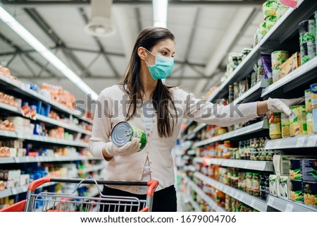 Woman preparing for pathogen virus pandemic spread quarantine.Choosing nonperishable food essentials.Budget buying at a supply store.Pandemic quarantine preparation.Emergency to buy list #1679004706