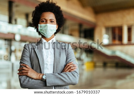 Portrait of African American woman wearing protective mask while standing with arms crossed at the airport during virus epidemic.  #1679010337