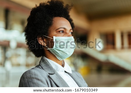 Pensive African American businesswoman wearing face mask while waiting at airport terminal during virus pandemic. #1679010349