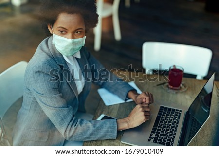 Pensive black businesswoman using laptop while sitting in a cafe with protective mask on her face. Royalty-Free Stock Photo #1679010409