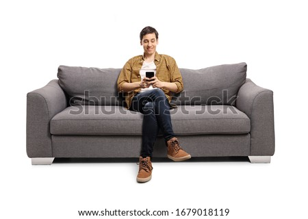 Happy young man sitting on a gray sofa and typing on a mobile phone isolated on white background Royalty-Free Stock Photo #1679018119