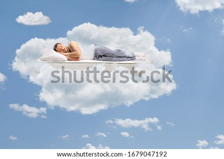 Man in pajamas sleeping on a mattress and floating in the sky surrounded by clouds #1679047192