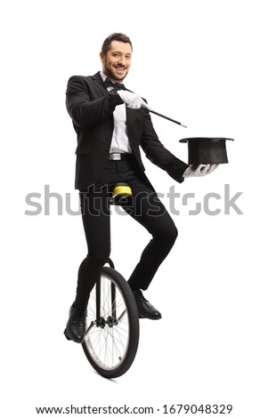 Full length portrait of a magician on a unicycle performing a hat trick isolated on white background #1679048329