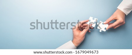 The man and woman holds in hand a jigsaw puzzle. Business solutions, success and strategy concept. Royalty-Free Stock Photo #1679049673