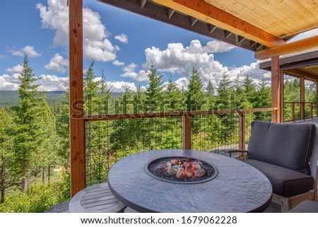 Amazing balcony patio with fire pit and forest and mountains view. Dream come true home exterior. New American architecture. Comfortable and beautiful home details. #1679062228