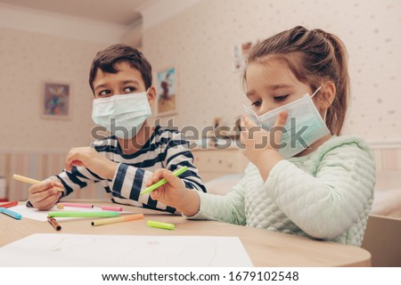 Cute children boy and girl in medical mask is sitting at home in quarantine. Сhildren play constructor after disinfection hands.  Entertainment for the children during  quarantine. Self isolation      #1679102548