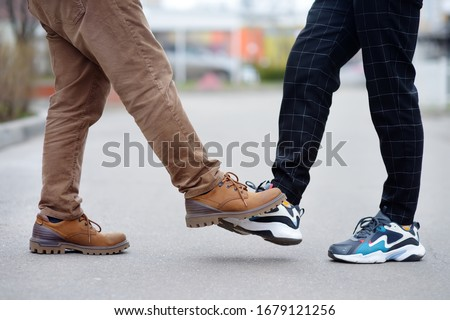Men greeting each other with foot instead of handshake. Friends or colleagues touch feet. Alternative non-contact greeting during coronavirus epidemic. Safety while COVID-19. Outbreak of Sars-cov-2 #1679121256