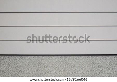 Front view of white artificial wood with stone pattern of gray Sheetrock in wall design background, cheap house materials prices in home architecture concept