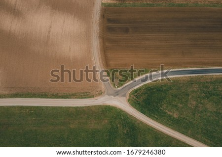 Vertical aerial photo of different fields covered with manure or fertilizer. Spring photo of brown fields with visible fertilizer on them, also crossroads of paths. #1679246380