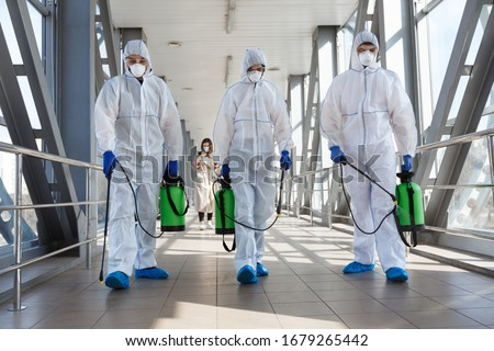 Specialist in hazmat suits cleaning disinfecting coronavirus cells epidemic, pandemic health risk Royalty-Free Stock Photo #1679265442
