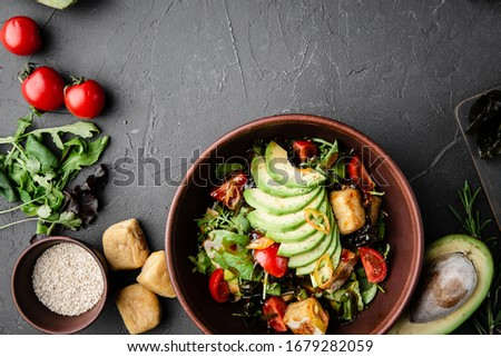 Chinese dishes in a clay plate on a black concrete background with ingredients for delivery #1679282059