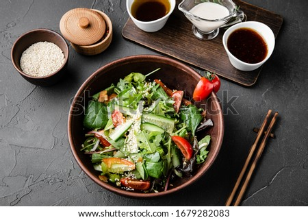 Chinese dishes in a clay plate on a black concrete background with ingredients for delivery #1679282083