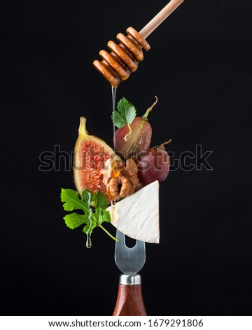 Camembert cheese on a fork (cheese knife) with figs, grapes, walnuts, honey and decor, cheese plate on a fork with honey stick, gourmet food concept #1679291806