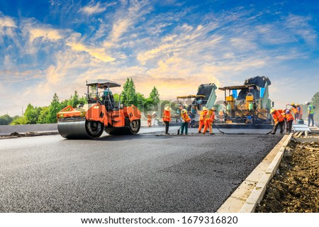 Construction site is laying new asphalt road pavement,road construction workers and road construction machinery scene.highway construction site landscape. Royalty-Free Stock Photo #1679316820