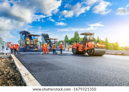Construction site is laying new asphalt road pavement,road construction workers and road construction machinery scene.highway construction site landscape. #1679321350