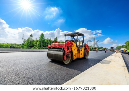 Construction site is laying new asphalt road pavement,road construction workers and road construction machinery scene.highway construction site landscape. #1679321380