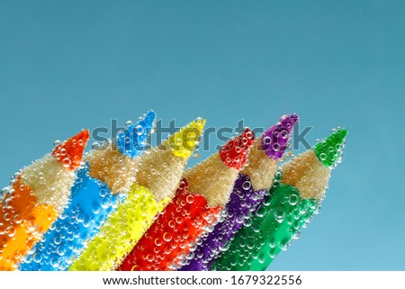 Abstract background. Pencils of different colors in air bubbles. Colored pencils of water with water. Texture of bubbles on pencils. Close-up, cropped shot, horizontal, free space at the top.