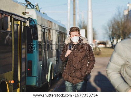 COVID-19 pandemic coronavirus a person near buses wearing a protective mask to spread the 2019 coronavirus disease. A man with a surgical mask on his face against SARS-cov-2. #1679333734