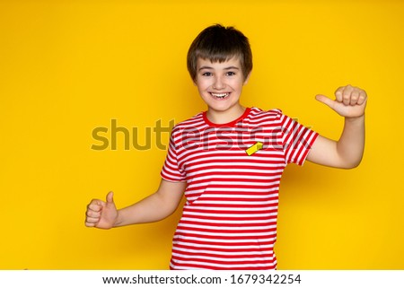 child 11-12 years old on a yellow background in a red T-shirt, various emotions of adolescence #1679342254
